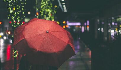 Synkkä syysää ja punaisen sateenvarjon alla kulkeva ihminen