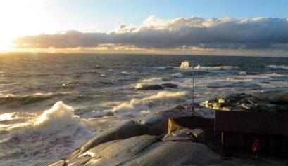 Rantakalliot, merimaisema ja aaltoja, jotka lyövät rantakallioihin